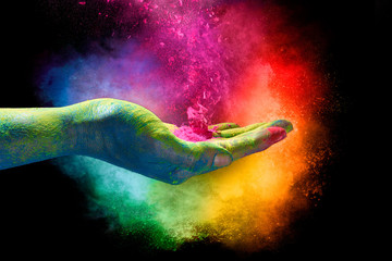 Magical rainbow colored dust exploding from a hand. Holi Festival Wall mural