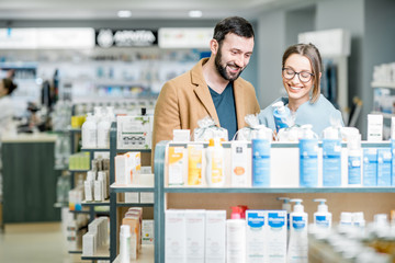 Poster Pharmacie Couple choosing cosmetics in the pharmacy