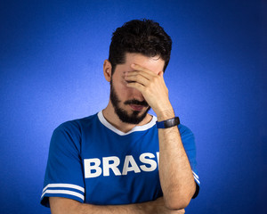 Brazilian supporter of National Team of football is looking down, depressed, worried.
