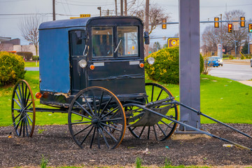 Outdoor view of old Amish carriage parked at one side of the rural road in Lancaster County
