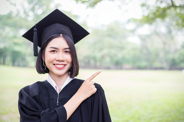 Portrait of young asian woman outside the building on her graduated day. Cute asian girl with her hand finger point to copy space area, Education success graduate concept