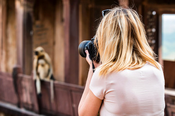 Beautiful girl takes picture of monkey in India