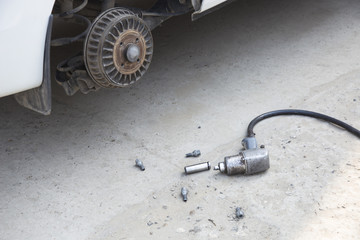 Air impact wrench on the ground, close-up image, near the car with the wheel removed
