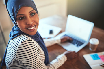 Smiling Arabic female entrepreneur working online in her home of