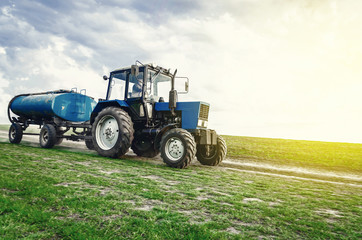 tractor of blue color with a barrel trailer rides along the spring field along the road