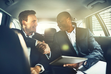 Smiling businessmen shaking hands in the backseat of a car