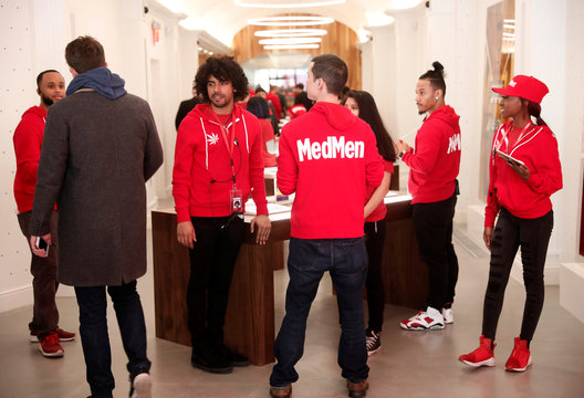 Customers and staff are seen inside MedMen, a California-based cannabis company store serving medical prescription patients with cannabis products, on the store's opening day on 5th Avenue in Manhattan in New York City