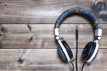 Headphone with jeans jacket on an antique wooden table