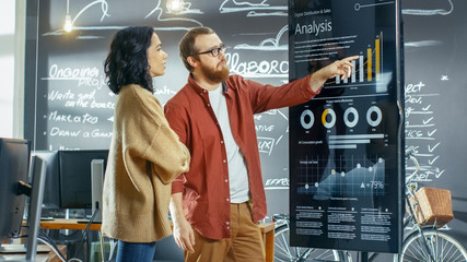 Female Developer and Male Statistician Use Interactive Whiteboard Presentation Touchscreen to Look at Charts, Graphs and Growth Statistics. They Work in the Stylish Creative Office. Wall mural