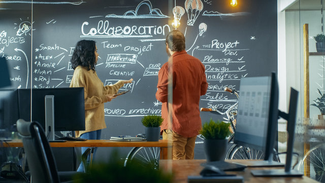 Female Project Manager Holds Tablet Computer and Shows Plan Drawn on a Blackboard Wall to Male Developer. They Work in the Creative Agency.
