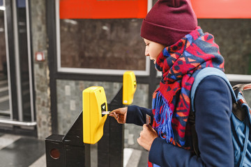 Woman validate ticket in machine device to entering at metro station in Prague