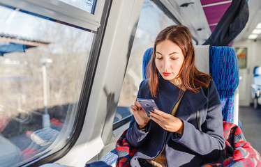 Traveler girl use mobile phone on the train, travel application concept