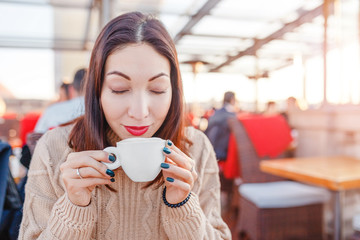woman drinking coffee in cafe on terrace