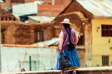 Woman in typical Peruvian costume and braids walks down a street in Puno (Peru)