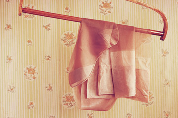 Vintage silk stockings on the wooden hanger against a background of the old wallpaper