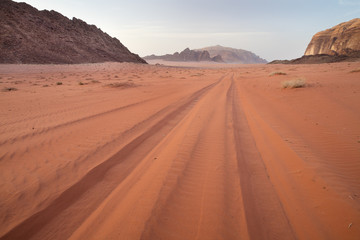 car trails in red sand in desert Wadi Rum in Jordan