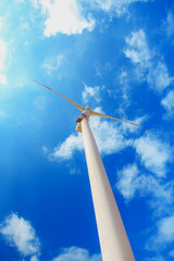 wind turbine on blue sky background with clouds