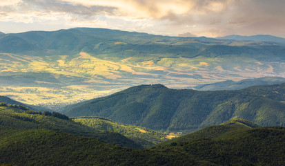 sun lit valley in afternoon. beautiful mountainous landscape and cloudy sky in golden light. lovely scenery after the storm. view from the top of a hill