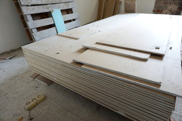 A pack of plasterboard is on the construction site in a room prepared for repair and decoration of a dwelling