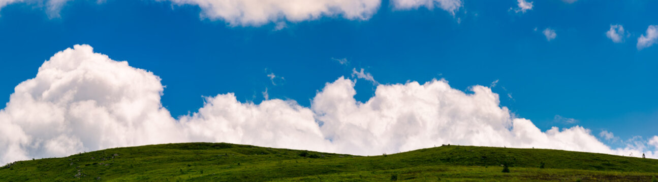 cloud rising behind the grassy hills. lovely panorama of cloudscape on a blue sky