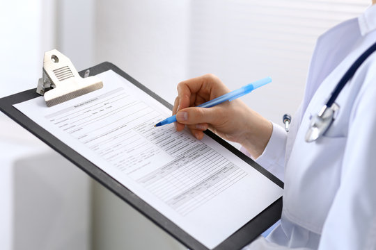 Female doctor filling up medical form on clipboard closeup.  Physician finishing up examining his patient in hospital and ready to give a prescription to help. Healthcare, insurance and medicin