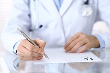 Doctor writing prescription form while sitting at glass desk in hospital, closeup view.  Healthcare, insurance and excellent service in medicine concept
