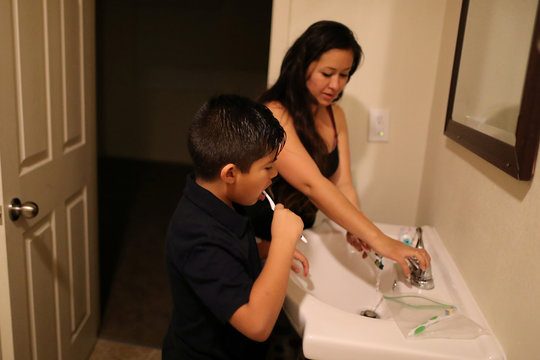 Yuritzy Quinones, 29, brushes her teeth with her son, True Garcia, 8, in Los Angeles