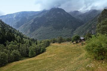 Prado entre montañas en un dia parcialmente nublado.