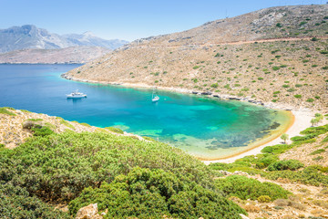 Beautiful sunny holiday coast view to the greek blue sea with crystal clear water beach relaxing with some boats fishing cruising surrounded by hills mountains, Patmos, Kos Island, Dodecanese, Greece