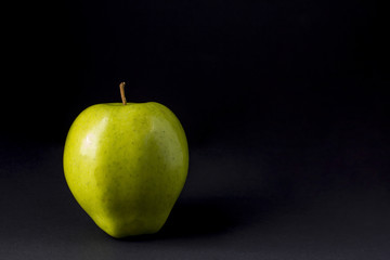 A green apple on a black background