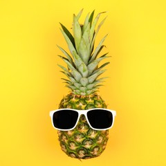 Hipster pineapple with sunglasses. Top view against a yellow background. Minimal summer concept.
