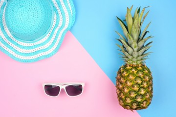 Pineapple with summer fashion accessories. Top view against a pink and blue background.