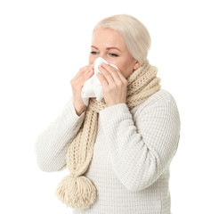 Mature woman with tissue suffering from cold on white background