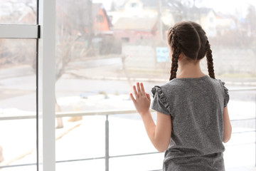 Lonely little girl near window indoors. Child autism