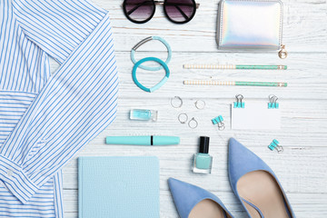 Flat lay composition with clothes, cosmetics and stylish accessories on light background