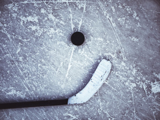 hockey puck and stick laying on the textured ice close up copyspace