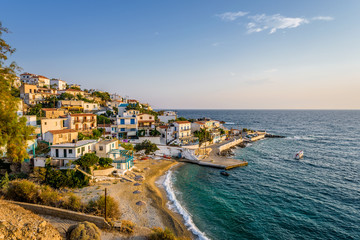 Beautiful colorful purple greek sunset sunrise coast view to a small greek town village with harbour fishing boats blue sea with crystal clear water, Ikaria Island, Armenisits, Sporades, Greece