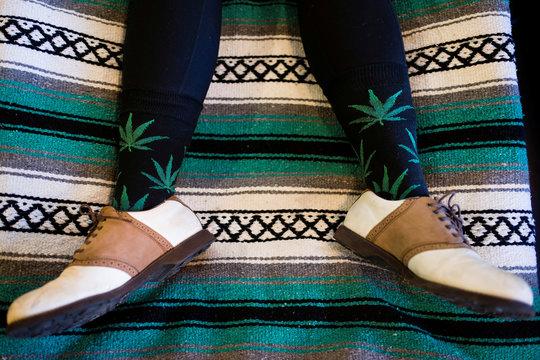 Hannah Landau wears marijuana-themed socks while using light therapy at the new Magnolia cannabis lounge in Oakland
