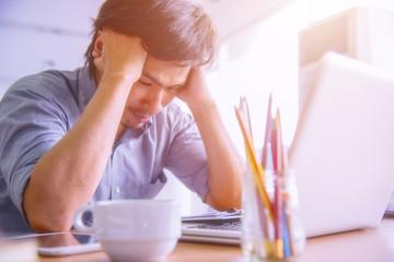 Man strain on earnings at office desk