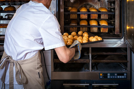 A male baker in white uniform and a beige apron bakes bread and takes cheese buns from an industrial oven. Work at the bakery
