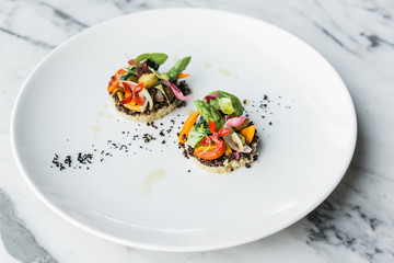 Quinoa canapes topping with pan seared asparagus, tomato and baby vegetables and olive oil served on white plate.
