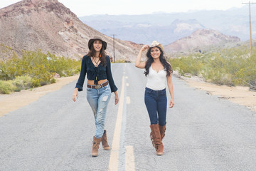 Two pretty country girls on a quiet road in the desert
