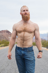 Strong, shirtless man alone on desert highway