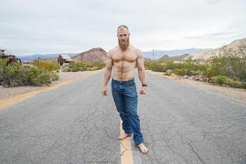 Strong, shirtless man alone on desert highway