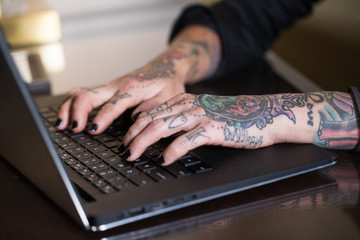 Tattoo hands typing on a laptop computer