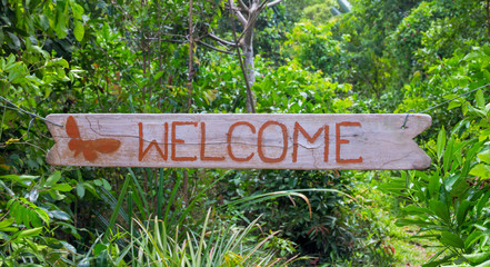 Welcome inscription by red paint on wooden board, green tropical garden background
