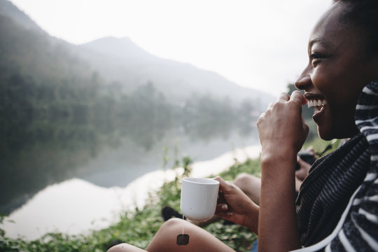 Woman enjoying morning coffee by a river