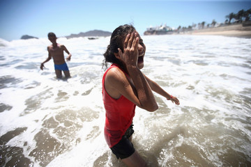 A Central American migrant, moving in a caravan through Mexico, gestures during a beach day in Mazatlan