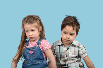 Close up emotional portrait of the smiling of the little  angry girl and  boy on blue background in studio.