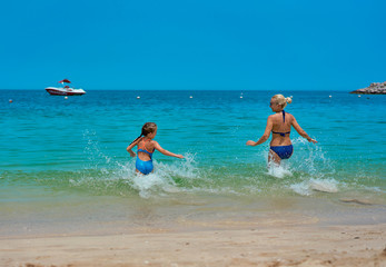 mom and daughter indulge on the beach